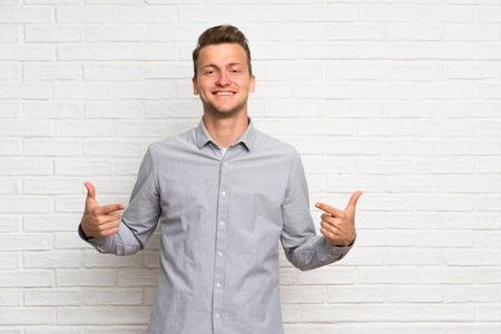 Hombre rubio sobre pared de ladrillo blanco orgulloso y satisfecho de sí mismo Foto de archivo