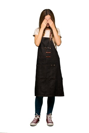 Full body Young woman with apron with tired and sick expression on isolated background 版權商用圖片