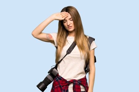 Young photographer woman with tired and sick expression on isolated blue background