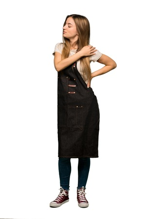 Full body Young woman with apron suffering from pain in shoulder for having made an effort on isolated background