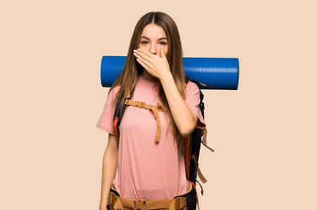 Young backpacker woman covering mouth with hands for saying something inappropriate on isolated yellow background Stock Photo