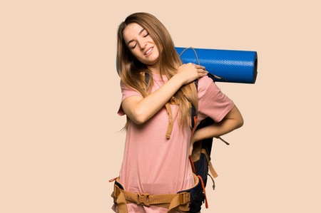 Young backpacker woman suffering from pain in shoulder for having made an effort on isolated yellow background Stock fotó