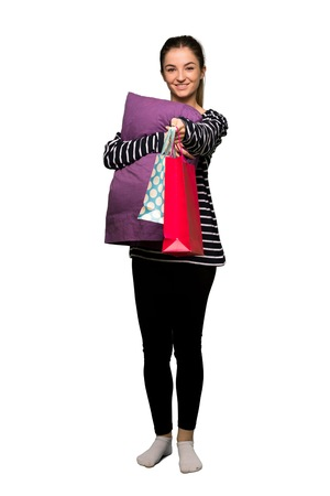 Full body Pretty woman in pajamas holding a lot of shopping bags on isolated background