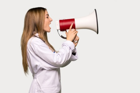 Young doctor woman shouting through a megaphone to announce something in lateral position on isolated grey background