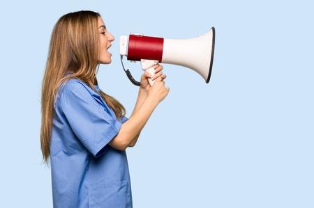 Jonge verpleegster die door een megafoon schreeuwt om iets aan te kondigen in zijpositie op geïsoleerde blauwe achtergrond Stockfoto