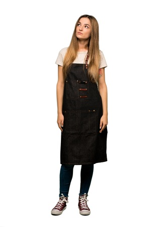Full body Young woman with apron looking up with serious face on isolated background