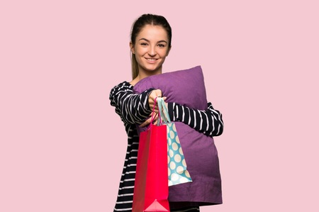 Pretty woman in pajamas holding a lot of shopping bags on isolated pink background