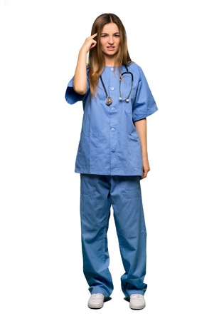 Full body Young nurse making the gesture of madness putting finger on the head on isolated background Stockfoto