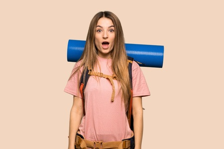 Young backpacker woman with surprise and shocked facial expression on isolated yellow background