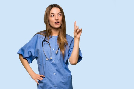 Young nurse thinking an idea pointing the finger up on isolated blue background