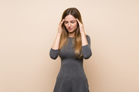 Young woman over isolated background with headache