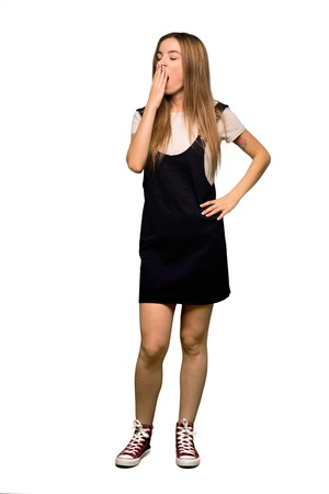 Full body Young pretty woman yawning and covering wide open mouth with hand on isolated background