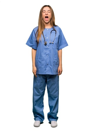 Full body Young nurse shouting to the front with mouth wide open on isolated background