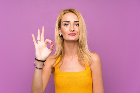 Young blonde woman over purple background showing an ok sign with fingers