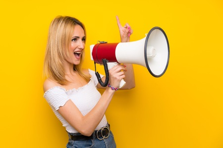 Young blonde woman over isolated yellow wall shouting through a megaphone