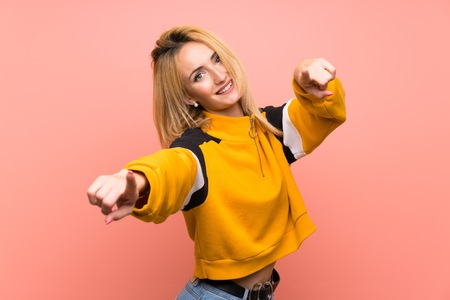 Young blonde woman over isolated pink background points finger at you while smiling