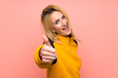 Young blonde woman over isolated pink background with thumbs up because something good has happened