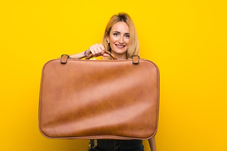 Young blonde woman over isolated yellow wall holding a vintage briefcase