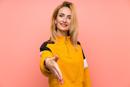 Young blonde woman over isolated pink background shaking hands for closing a good deal