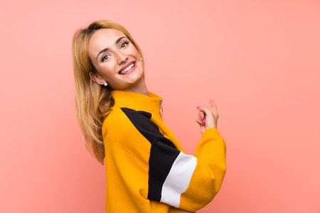 Young blonde woman over isolated pink background pointing back