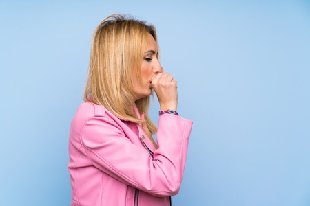 Young blonde woman with pink jacket over isolated blue background is suffering with cough and feeling bad