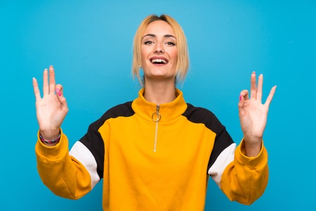 Young blonde woman over isolated blue background showing an ok sign with fingers