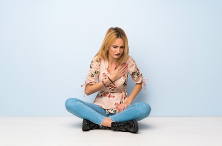 Young blonde woman sitting on the floor having a pain in the heart Фото со стока