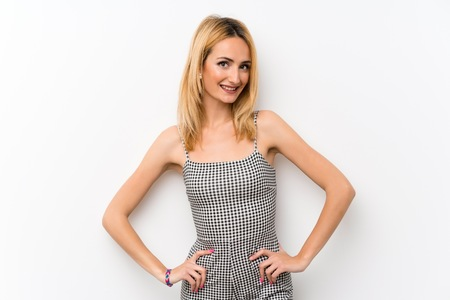 Young blonde woman over isolated white posing with arms at hip and smiling Stock Photo