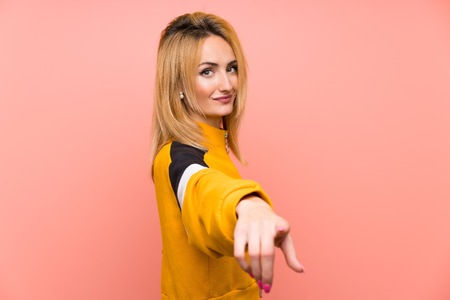 Young blonde woman over isolated pink background points finger at you with a confident expression