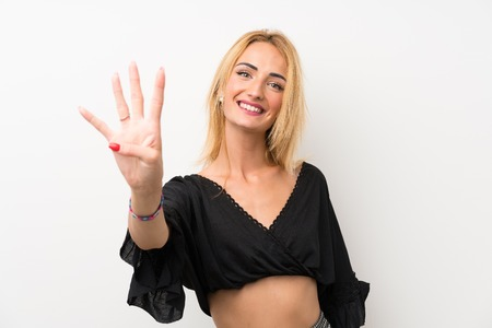 Young blonde woman over isolated white wall happy and counting four with fingers Banco de Imagens