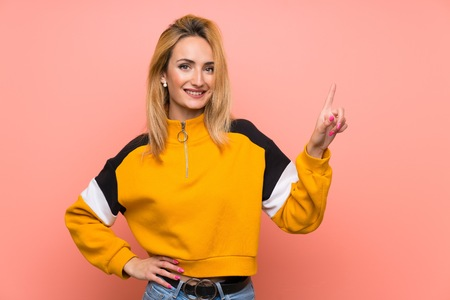 Young blonde woman over isolated pink background showing and lifting a finger in sign of the best Banco de Imagens