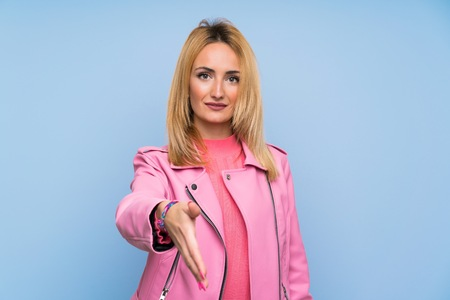 Young blonde woman with pink jacket over isolated blue background shaking hands for closing a good deal