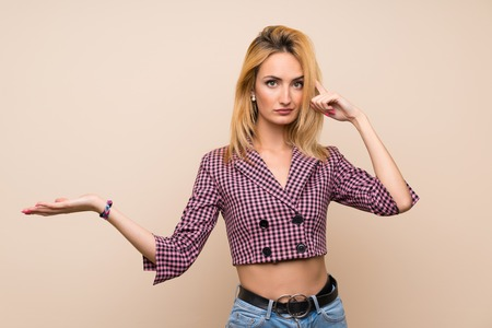 Young blonde woman with pink jacket over isolated wall making the gesture of madness putting finger on the head