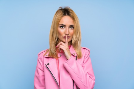Young blonde woman with pink jacket over isolated blue background showing a sign of silence gesture putting finger in mouth