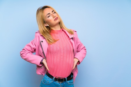 Young blonde woman with pink jacket over isolated blue background suffering from backache for having made an effort Stock Photo - 124767547