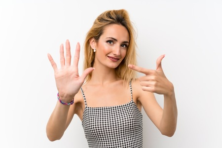 Young blonde woman over isolated white counting seven with fingers