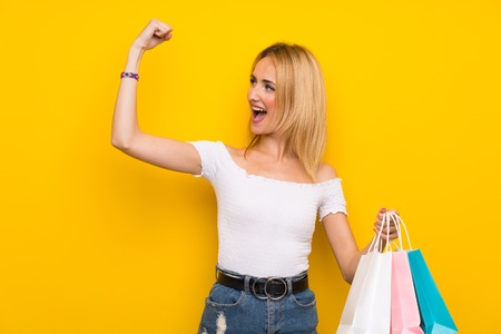 Young blonde woman over isolated yellow wall holding a lot of shopping bags Imagens - 124767551