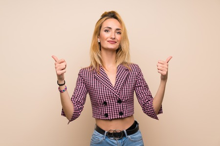 Young blonde woman with pink jacket over isolated wall with thumbs up gesture and smiling