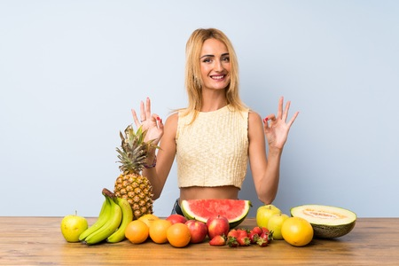Young blonde woman with lots of fruits showing an ok sign with fingers Stock Photo