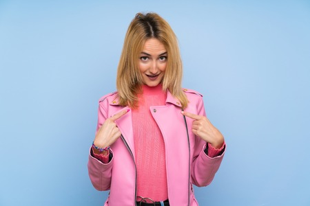 Young blonde woman with pink jacket over isolated blue background with surprise facial expression