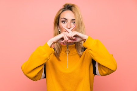 Young blonde woman over isolated pink background showing a sign of silence gesture