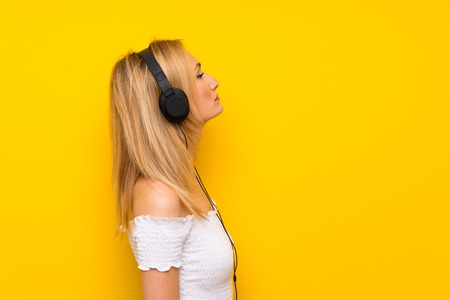 Young blonde woman over isolated yellow wall listening to music with headphones Reklamní fotografie