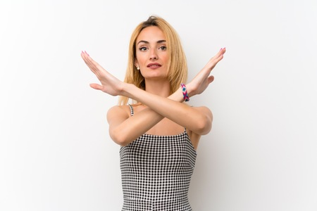 Young blonde woman over isolated white making NO gesture