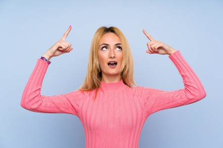 Young blonde woman with pink sweater over isolated blue background pointing with the index finger a great idea