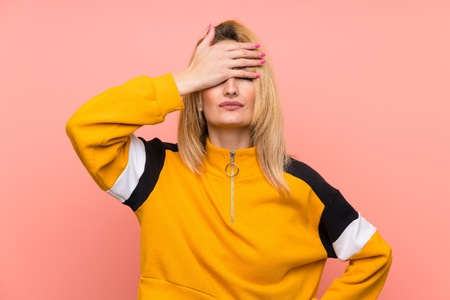 Young blonde woman over isolated pink background covering eyes by hands. Do not want to see something