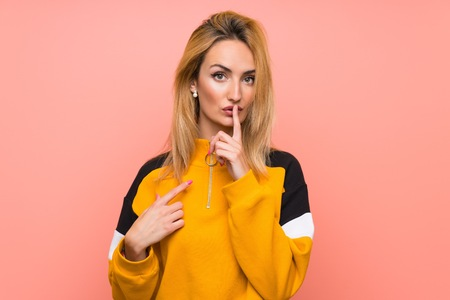 Young blonde woman over isolated pink background showing a sign of silence gesture putting finger in mouth Banco de Imagens