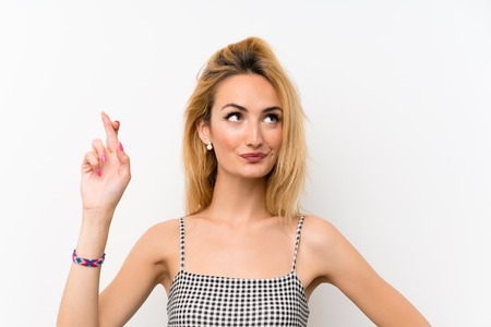 Young blonde woman over isolated white with fingers crossing and wishing the best