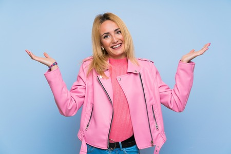 Young blonde woman with pink jacket over isolated blue background smiling a lot Imagens - 124770171