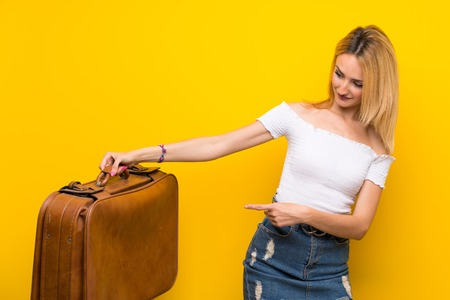 Young blonde woman over isolated yellow wall holding a vintage briefcase 版權商用圖片 - 124770175