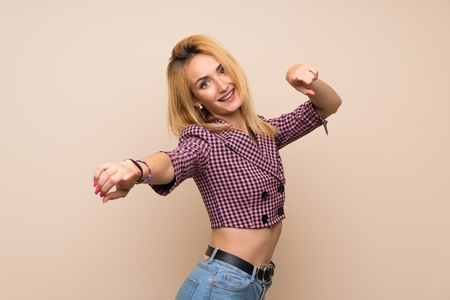 Young blonde woman with pink jacket over isolated wall points finger at you while smiling Banco de Imagens